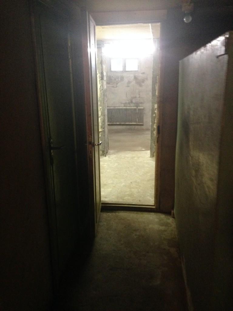 En korridor i källaren. Dörren till vänster leder in till toaletten, till höger står en gammal oljetank och rakt fram kommer garaget.